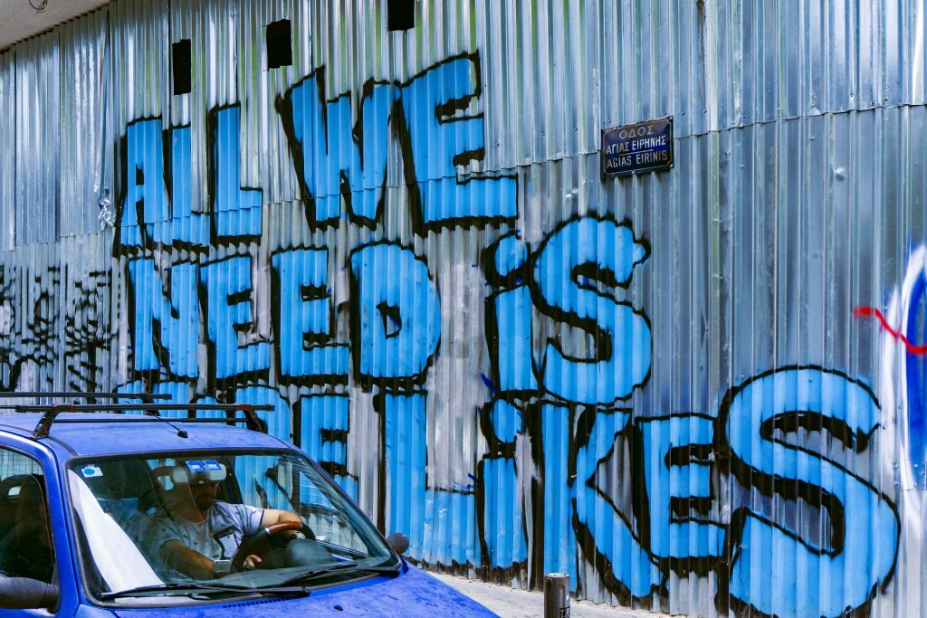 """Graffiti on wall that says """"All we need is more lIkes"""""""
