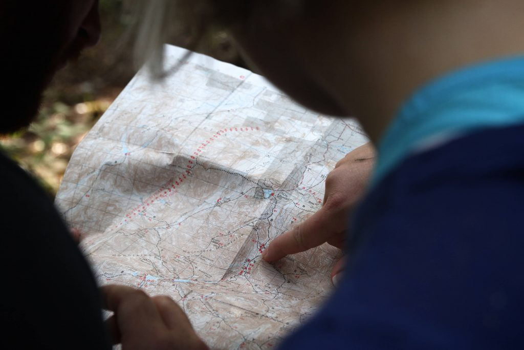 Person pointing to map showing trail