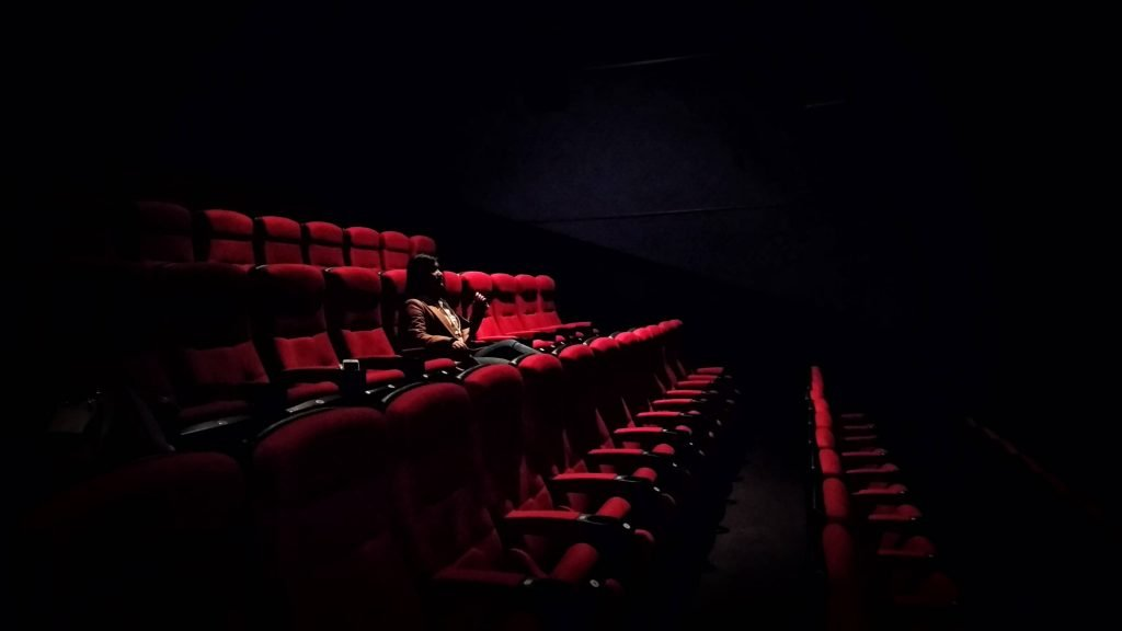 Empty seats around 1 girl in theater with light on her